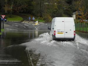 Freelance Courier delivering parcels in a White Van in Wet Weather