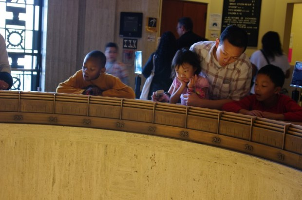 Young minds in the process of being blown by a Foucault Pendulum.