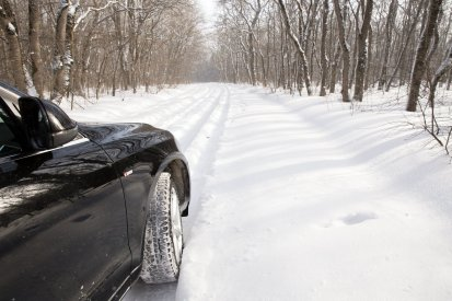 car driving in forest with much snow