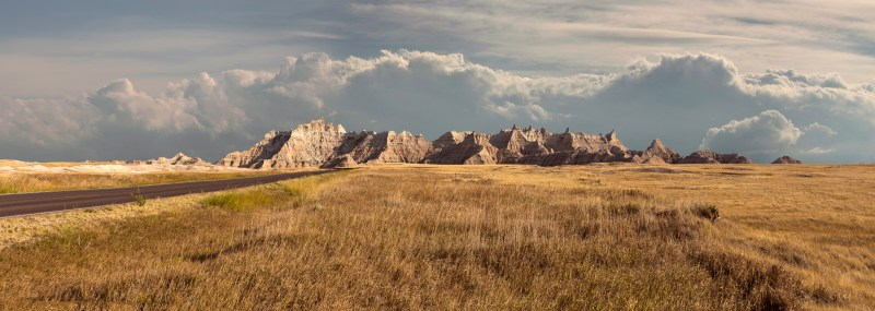 Panorama of badlands national park with vista of mountain range with large clouds in background
