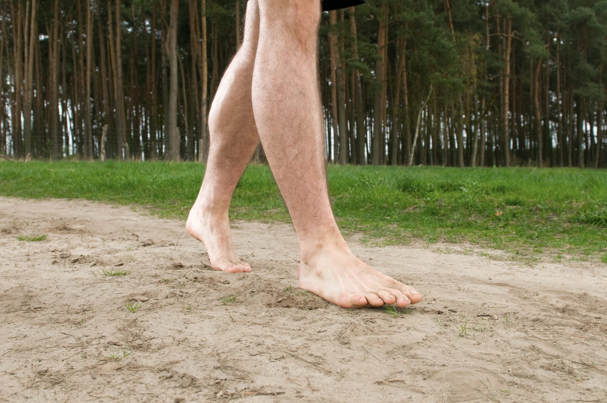 to-clad-legs-and-feet-of-a-young-man-on-a-sand-road-starting-with-wooded-background_t20_K6a1kK
