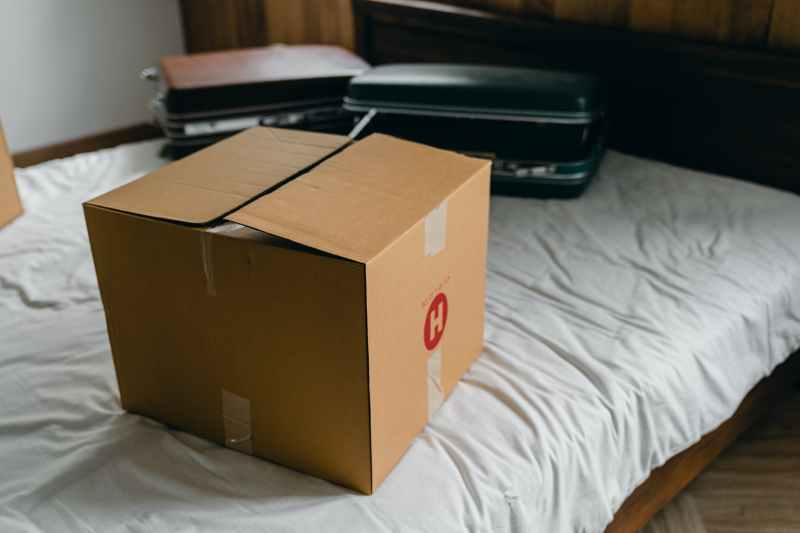 carton box and suitcases for relocation on bed