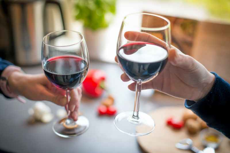 close up photo of two people toasting with red wine
