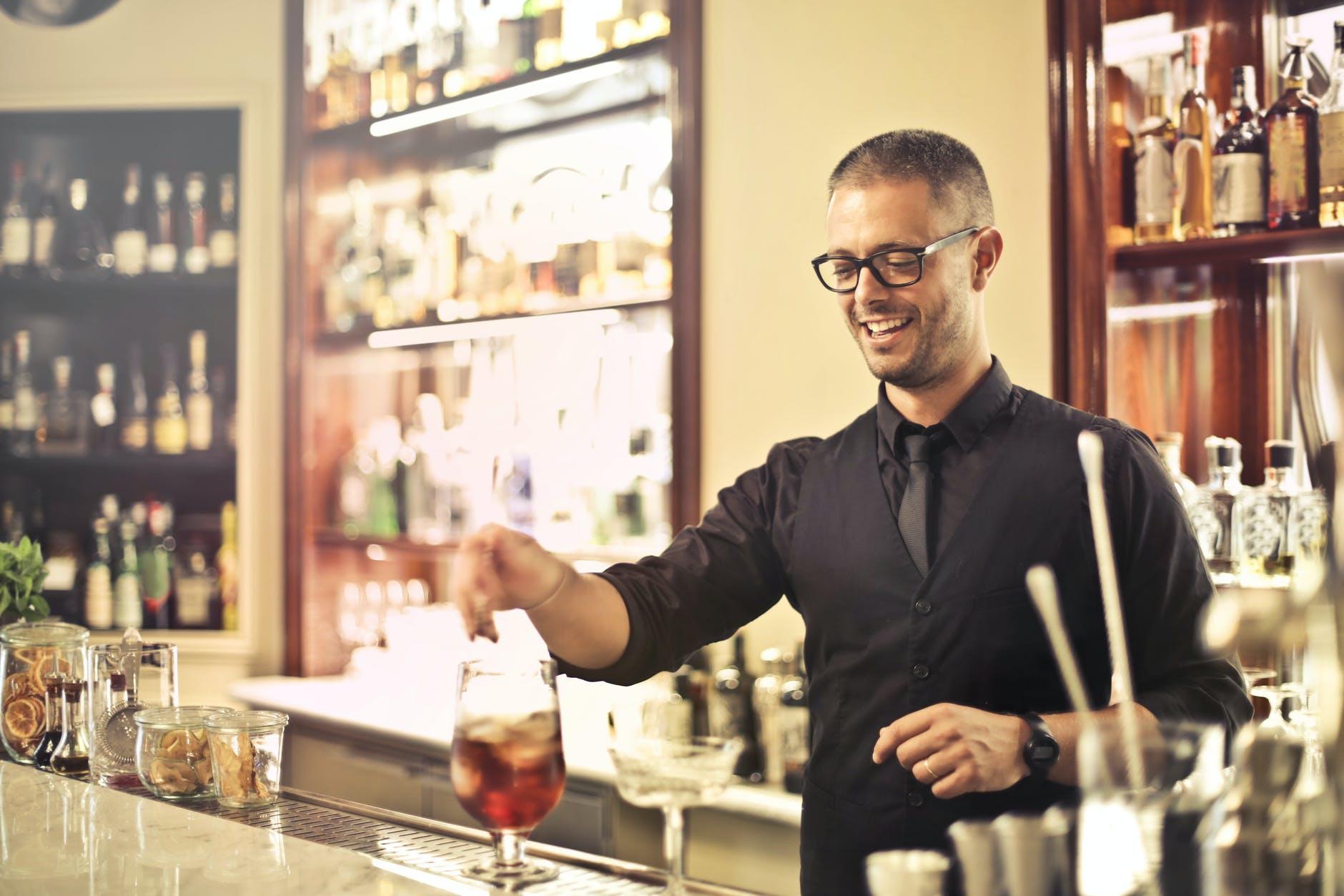 positive bartender preparing cocktail in pub