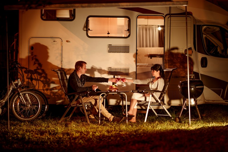 Couple drinking in front of their RV.