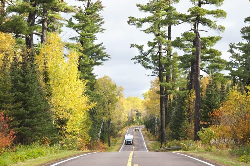Camper and pickup truck drive through fall forrest
