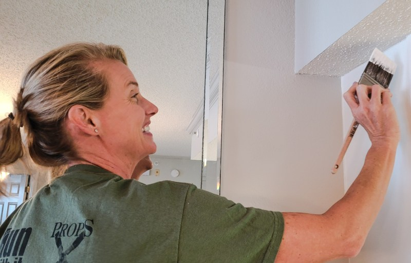 Woman white washing her cabinets