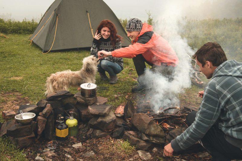 Friends sitting around campfire making food.