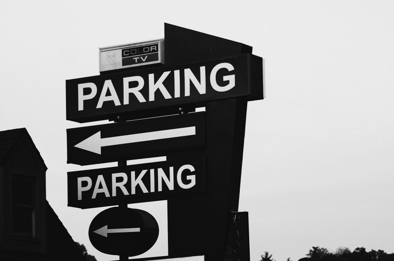 Black and white parking arrow sign.