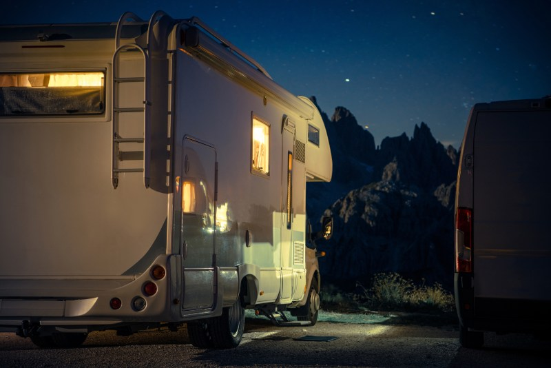 RV parked at night in a parking lot.