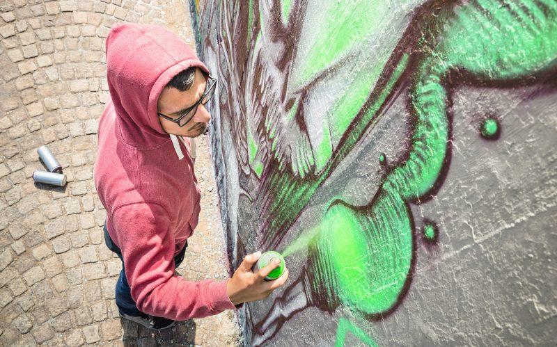 Man spray painting a mural