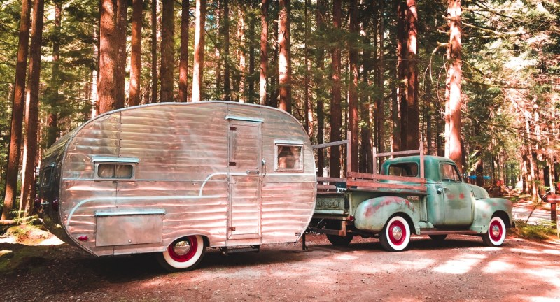 Vintage truck towing small travel trailer.