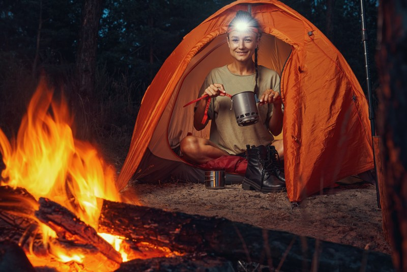 Woman camper sitting in tent by her campfire.