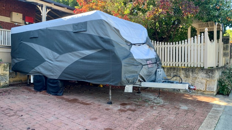 RV parked and properly stored with a cover.
