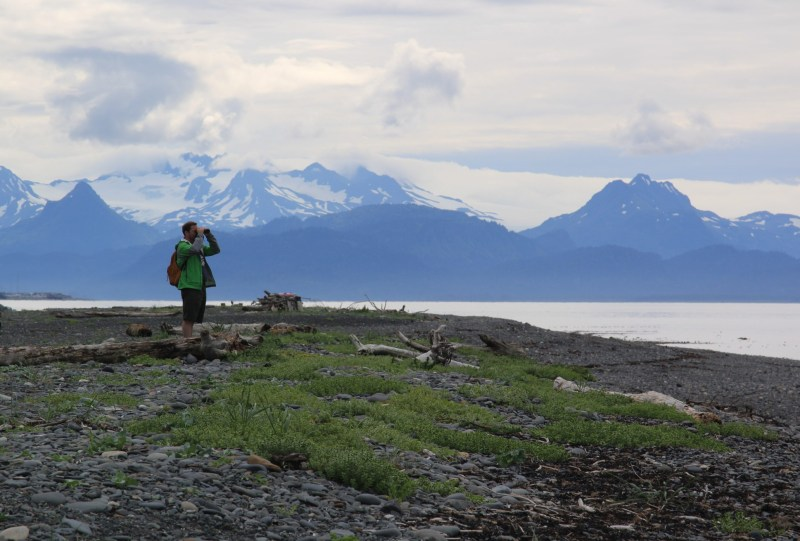 Man in Alaska using binoculars to look into the distance at Russia.