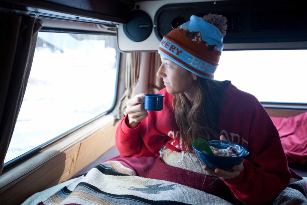 Woman in RV bed during winter.