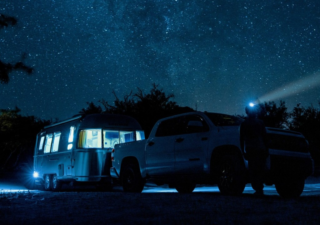 Truck with RV lights on parked under the stars.