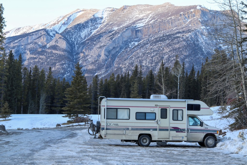 RV parked in a snowy parking lot.