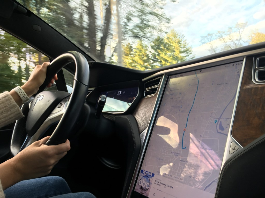 Woman using Tesla built in map while driving.