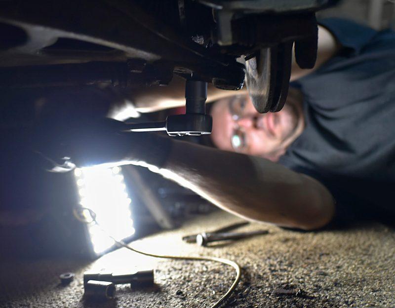 Male mechanic fixing axle.