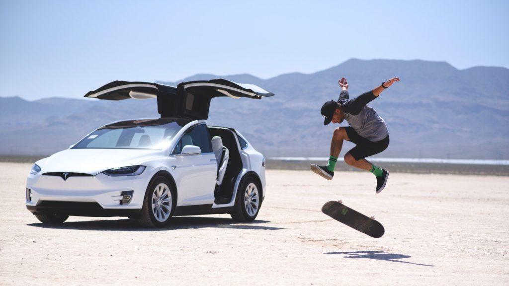Man skateboarding next to his Tesla.
