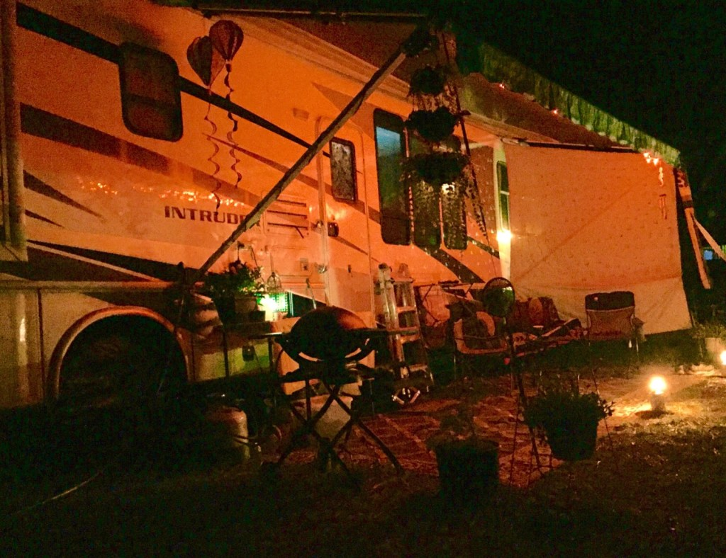 RV exterior with lights on at night.