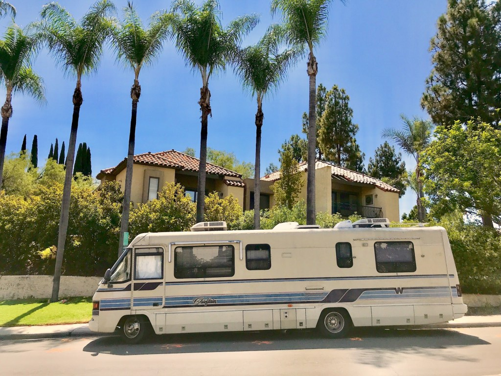 Vintage RV parked in front of house.