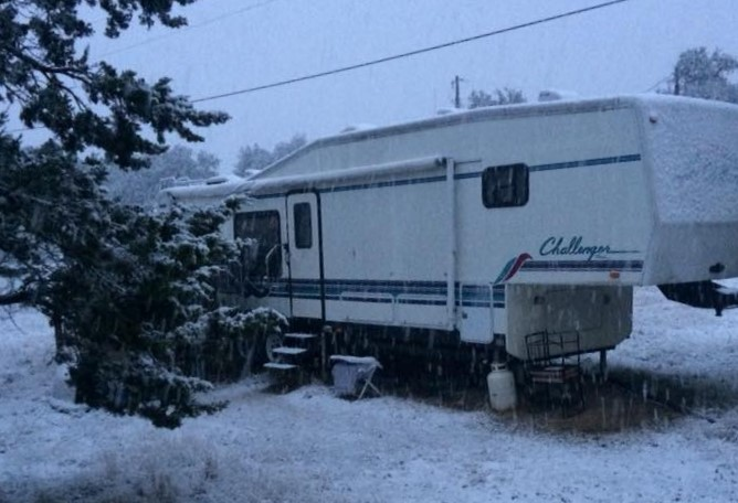 RV parked outside in the snow with no cover.