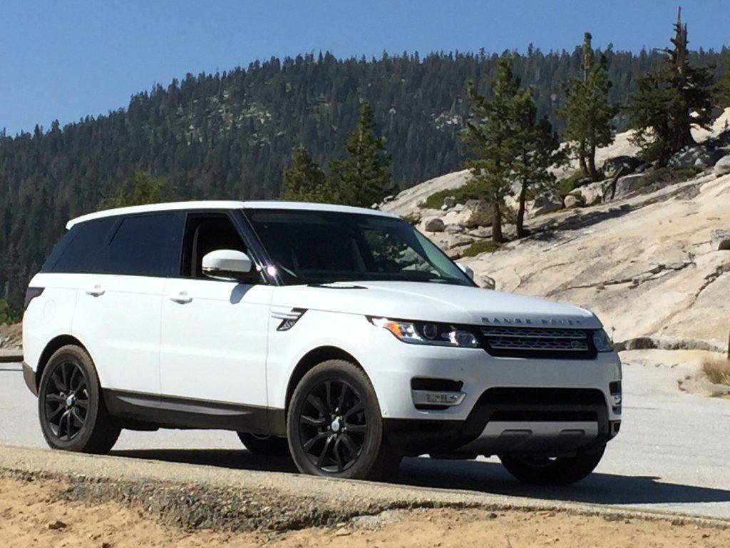 White range rover parked along mountain.