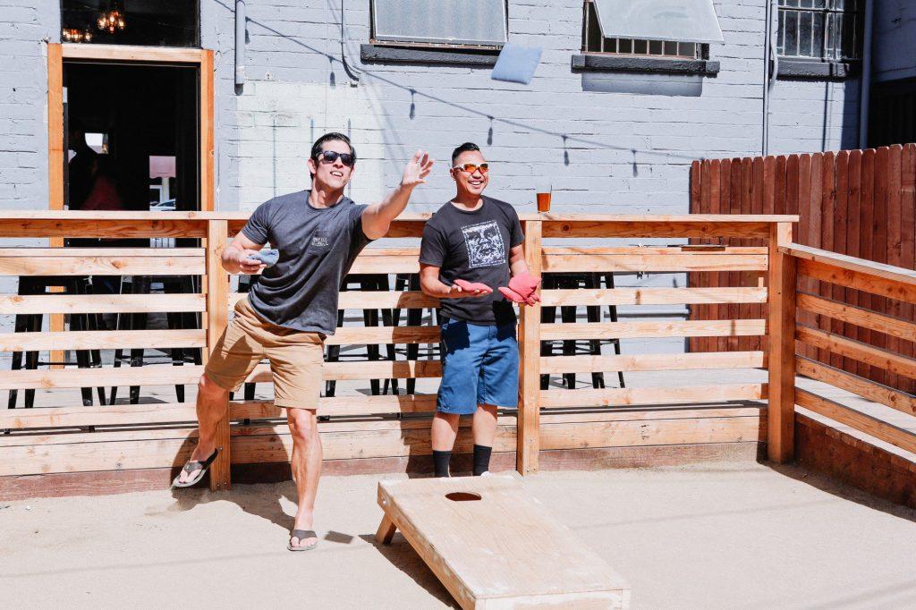 Two male friends playing cornhole.