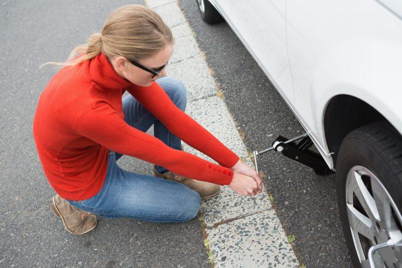 Woman repairing tire on vehicle.