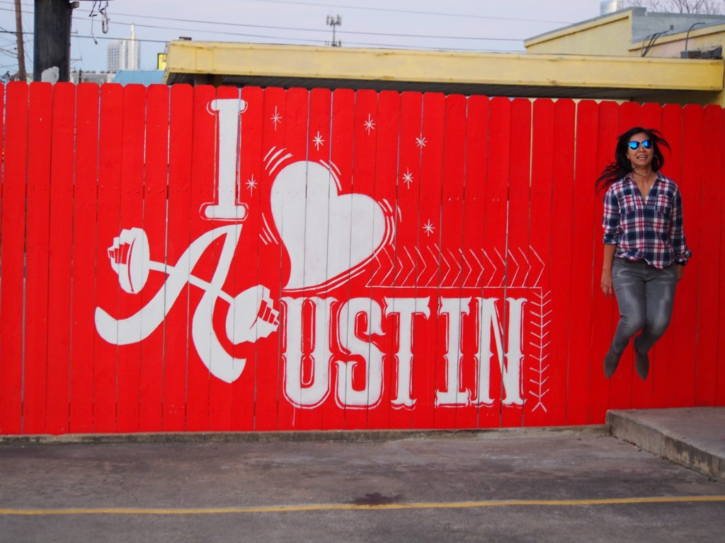 Woman jumping in front of I heart Austin sign.