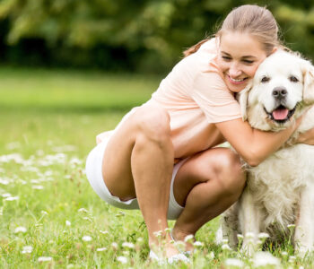 Frau umarmt glücklich ihren Hund auf einer Wiese im Sommer
