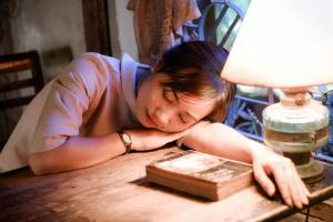 girl sleeping o n a table with lamp on and book on wooden desk
