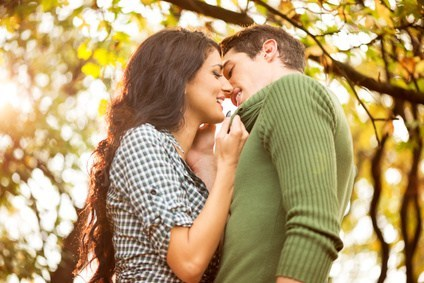 Happy couple kissing in the park during fall