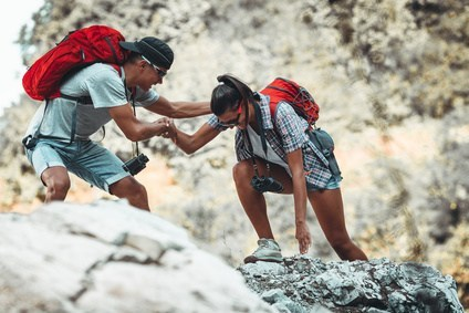 Young couple hiking and climbing at the mountain to represent Dr. Karen Gless' blog Work it Out – with a Lot Less Pain