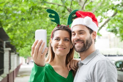Happy couple taking a picture in Christmas season