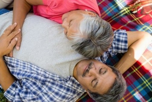 Senior couple laying on blanket