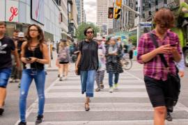 people walking in crosswalk downtown as if they're walking into the unknown