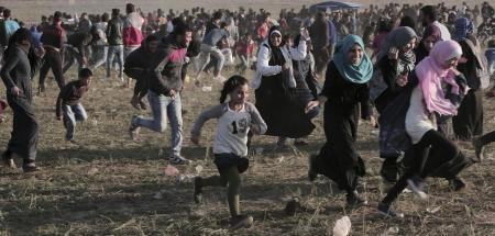 Palestinian-protesters-run-for-cove