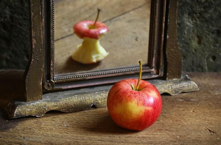 Ein Apfel vor dem Spiegel. Im Spiegelbild ist der Apfel aufgegessen.
