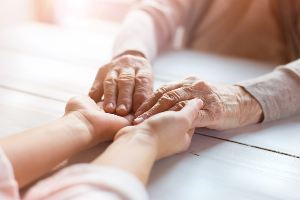 elderly couple holding hands across table