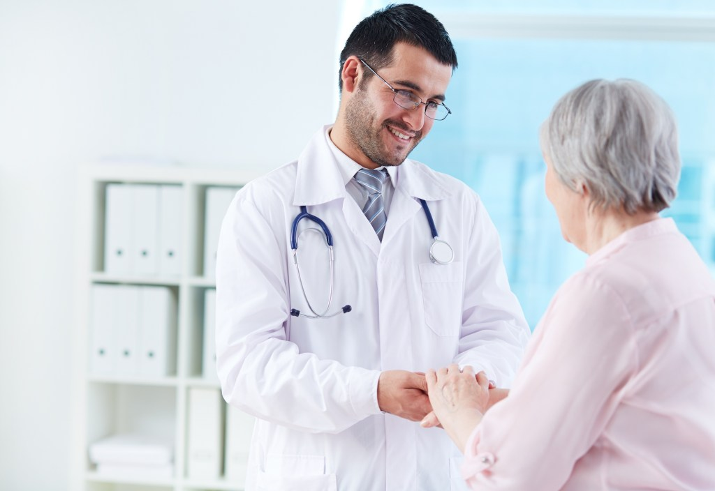 male doctor with glasses talking to grandmother