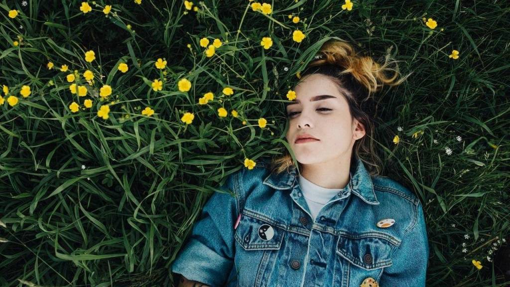 woman with demin coat on asleep in a field of flowers