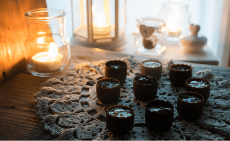 table lit with candle light and nine chocolate peanut butter cup vegan cannabis edibles