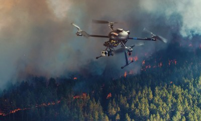 A small UAV is shown surveying the movement of a forest fire. The EOAMS would allow first responders to deploy drones at disaster scenes without endangering other emergency response aircraft or commercial flights. [photo illustration by Kongsberg Geospatial]