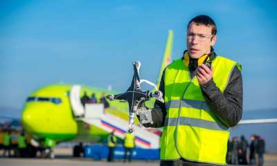 An airport worker holding crashed quadcopter near airliner | Mark Agnor