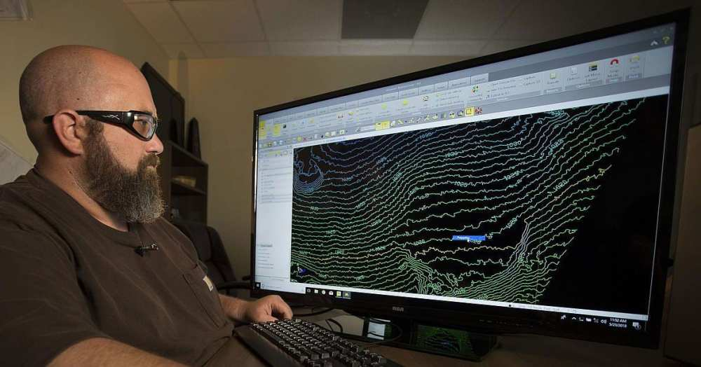 An engineer reviews a topographical map captured by a drone equipped with geomatics equipment | Microdrones