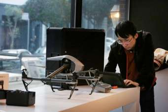 Ken Chen, Magic Sky sales associate, works next to a DJIInspire drone at the DJI store on Montgomery Street in San Francisco, as he prepared for that store to open in February.