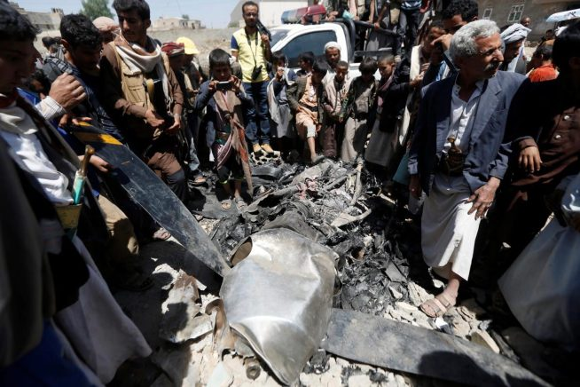 People gather around the engine of a drone aircraft which the Houthi rebels said they have downed in Sanaa, Yemen October 1, 2017. REUTERS:Khaled Abdullah